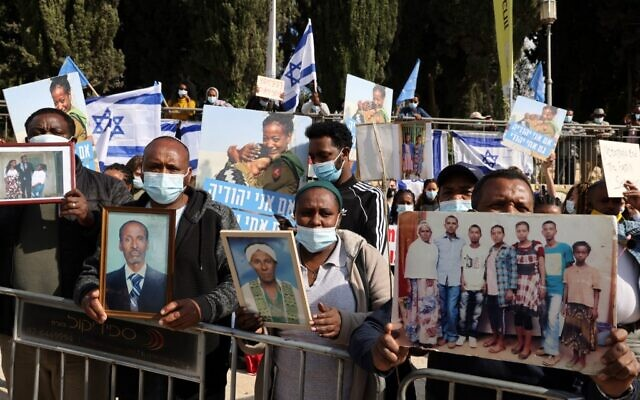 Members of the Jewish Ethiopian community hold up photographs of their relatives outside the Prime Minister's Office in Jerusalem on November 25, 2020, during a demonstration demanding to bring thousands of their remaining brethren from Ethiopia to Israel. (Menahem Kahana/AFP)