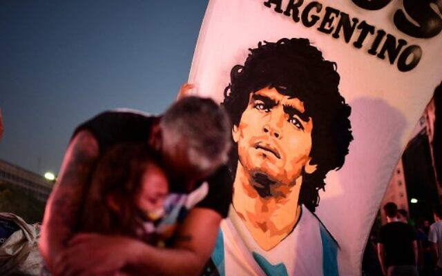A father and her daughter, fans of Argentinian football legend Diego Maradona, mourn as they gather by the Obelisk to pay homage on the day of his death in Buenos Aires, on November 25, 2020. (Photo by RONALDO SCHEMIDT / AFP)