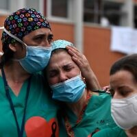 Healthcare workers ackwoledge applause in memory of their co-worker Esteban, a male nurse that died of the coronavirus disease at the Severo Ochoa Hospital in Leganes, near Madrid, on April 10, 2020. (PIERRE-PHILIPPE MARCOU / AFP)