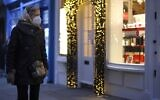 A pedestrian wearing a protective face covering to combat the spread of the coronavirus, walks past the Christmas-themed window displays of shops in central London on November 27, 2020, as life under a second lockdown continues in England. (Tolga Akmen / AFP)