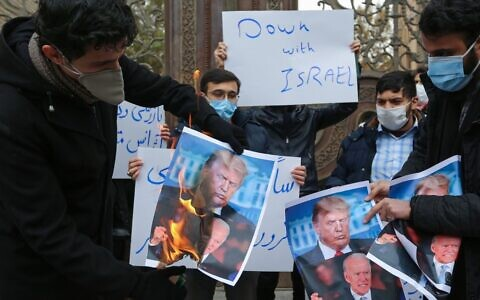 Students of Iran's Basij paramilitary force burn posters depicting US President Donald Trump (top) and President-elect Joe Biden, during a rally in front of the foreign ministry in Tehran, on November 28, 2020, to protest the killing of prominent nuclear scientist Mohsen Fakhrizadeh a day earlier near the capital. (Atta Kenare/AFP)
