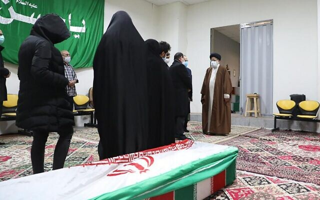 Iran's Judiciary Chief Ayatollah Ebrahim Raisi (R) pays respects to the body of slain scientist Mohsen Fakhrizadeh among his family, in the capital Tehran on November 28, 2020. (MIZAN NEWS AGENCY / AFP)