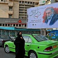 A woman walks by a billboard honoring nuclear scientist Mohsen Fakhrizadeh in the Iranian capital Tehran, on November 30, 2020. (Atta Kenare/AFP)