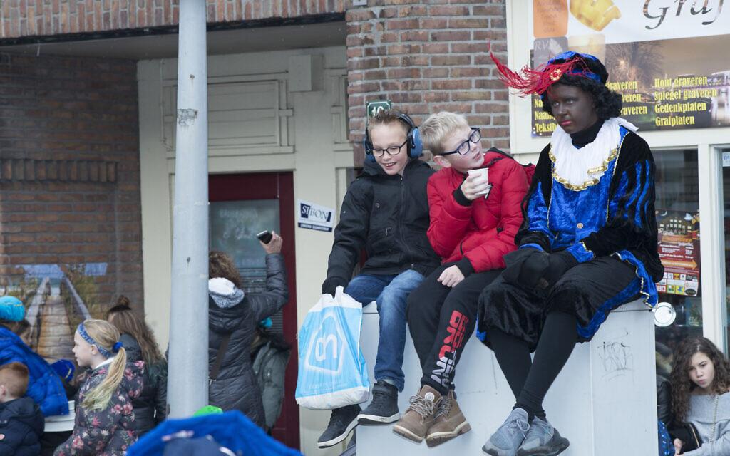 Children chat during a Black Pete event in Amsterdam, November 16, 2019. (Cnaan Liphshiz/ JTA)