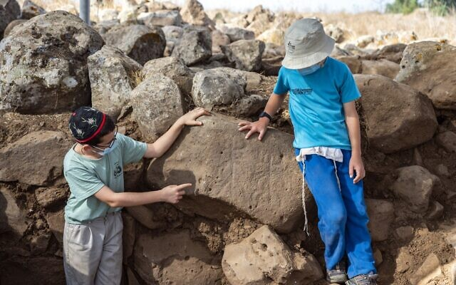 Children from the religious community of Hispin in the Golan volunteering at the excavation, pointing to the engraved figures dating to circa 11th century BCE, at a fort which could be the earliest evidence of the biblical 'Geshurites.' (Yaniv Berman, Israel Antiquities Authority)
