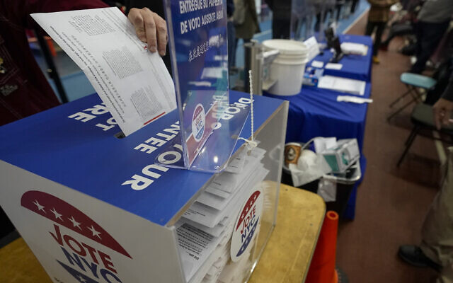 A voter drops an absentee ballot in a locked ballot box during early voting at the Park Slope Armory YMCA in Brooklyn, New York, October 27, 2020. (Mary Altaffer/AP)