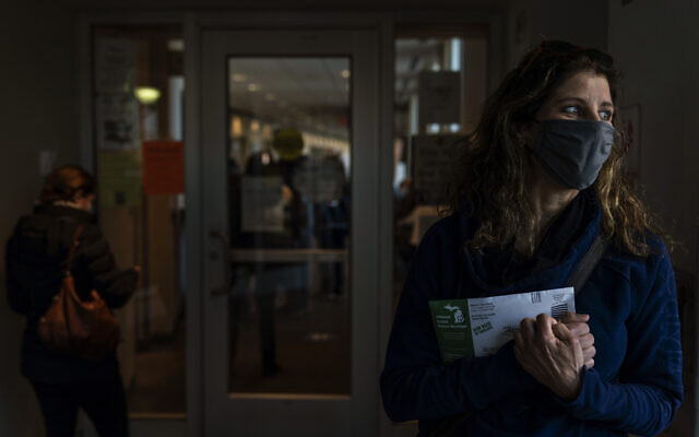 Diane Spiteri clutches her absentee ballot before dropping it off at the city clerk's office in Warren, Michigan,  October 28, 2020. (AP Photo/David Goldman)