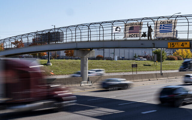 An Iraq and Afghanistan war veteran, who did not give his name, stands on a highway overpass with signs encouraging motorists to vote in Hamtramck, Michigan, October 28, 2020. (AP Photo/David Goldman)