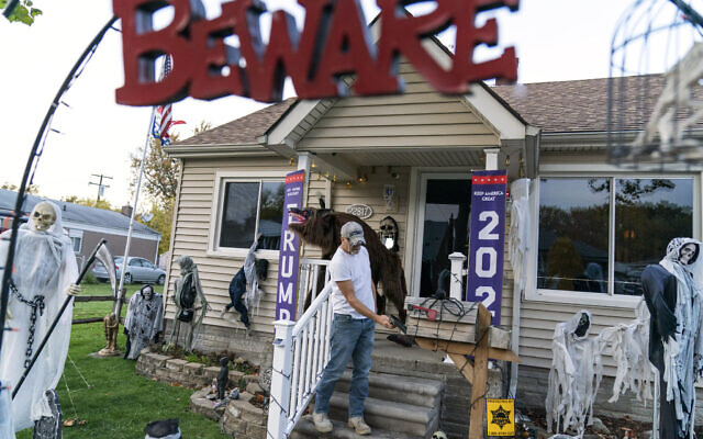 Trump supporter Terry Frandle checks his mailbox in his front yard decorated for Halloween and a Trump reelection campaign in Saint Clair Shores, Michigan, October 28, 2020. (AP Photo/David Goldman)