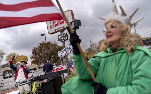 Trump supporters Carol Reed, dressed as the Statue of Liberty, right, and Matthew Woods, dressed as a Continental Army soldier, cheer at an intersection during a rally in Mount Clemens, Michigan, October 29, 2020. (AP Photo/David Goldman)