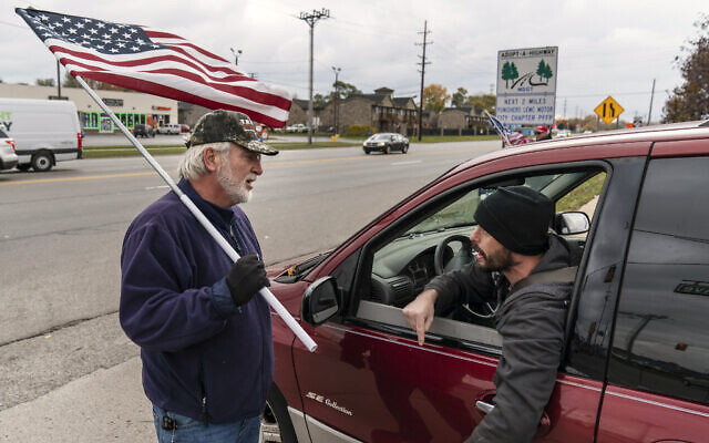 A passing motorist argues with Trump supporter Mike Jamerson during a rally at an intersection in Mount Clemens, Michigan, October 29, 2020. (AP Photo/David Goldman)