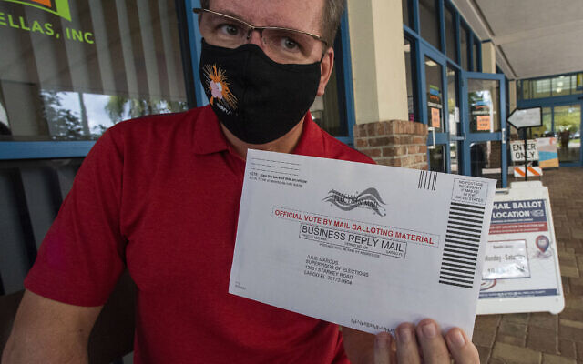 Charles Oppermann holds his vote by mail ballot for Joe Biden outside the drop-off location at the Dunedin Public Library, October 29, 2020. (AP Photo/Steve Nesius)