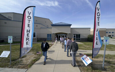 People wait to cast their ballot on the first day of early voting at an advance polling location October 17, 2020, in Overland Park, Kansas. (AP Photo/Charlie Riedel)