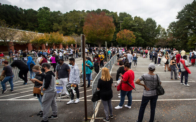 Hundreds of people wait in line for early voting on October 12, 2020, in Marietta, Georgia. (AP Photo/Ron Harris)