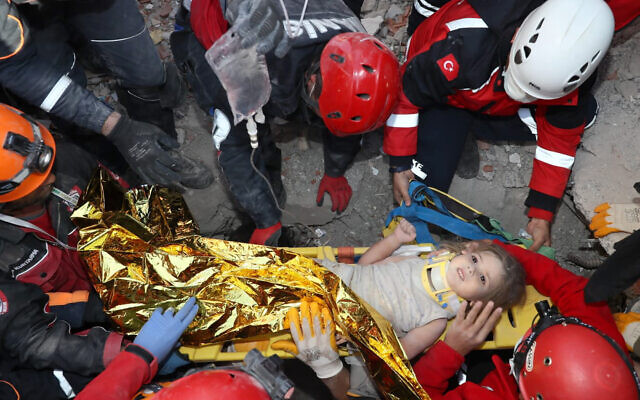 Rescue workers, who were trying to find survivors of an earthquake, surround Ayda Gezgin after they pulled the young girl out alive from the rubble of a collapsed apartment in the Turkish coastal city of Izmir, November 3, 2020, (AFAD via AP)