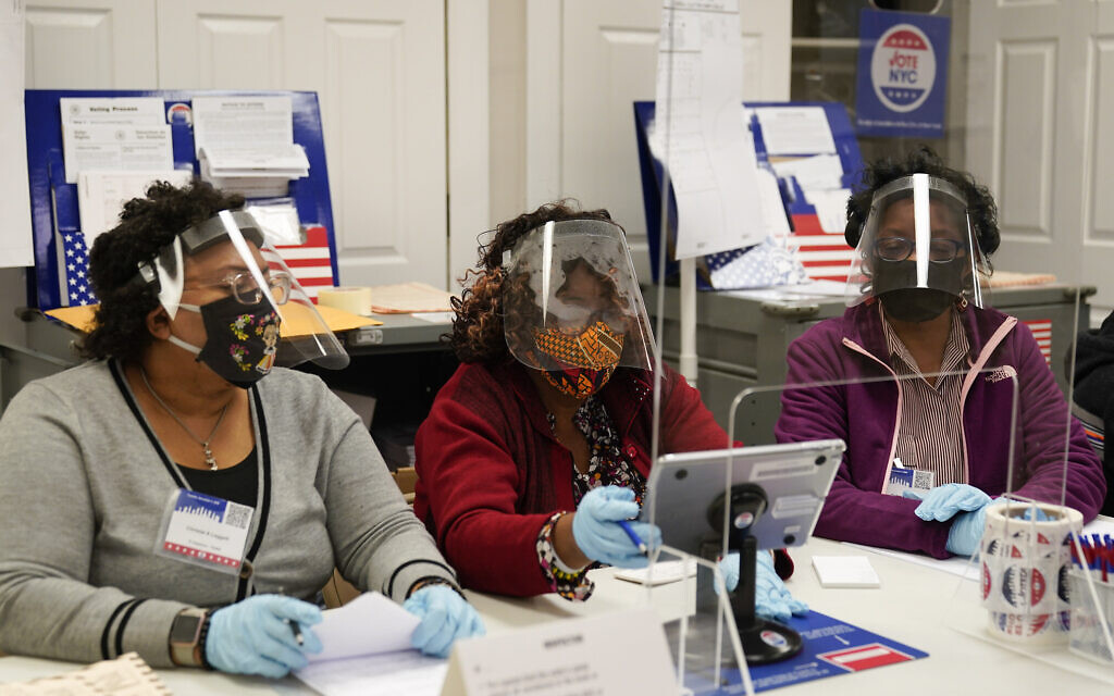 Election workers prepare to register voters on Election Day at a polling place inside the Bartow Community Center, November 3, 2020, in the Bronx borough of New York. (AP Photo/Mark Lennihan)
