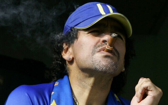 In this March 26, 2006, photo, former soccer player Diego Maradona smokes a cigar as he watches Argentina's first division soccer match between Boca Juniors and River Plate in Buenos Aires, Argentina. (AP Photo/Natacha Pisarenko, File)
