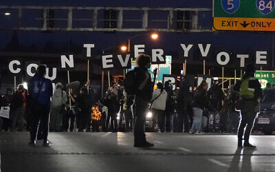 Protesters hold letters that spell Count Every Vote as they cross an overpass while marching in Portland, Oregon, November 4, 2020, following the US election. (AP Photo/Marcio Jose Sanchez)
