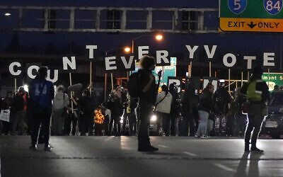 Protesters hold letters that spell Count Every Vote as they cross an overpass while marching in Portland, Oregon, November 4, 2020. (AP Photo/Marcio Jose Sanchez)