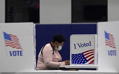 In this November 3, 2020, file photo, a woman votes at the MLB Urban Youth Academy in Kansas City, Missouri. (AP/Charlie Riedel, File)