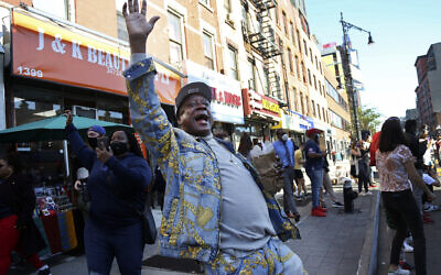 "Marcel Cothron sings ""Na na na na, hey hey goodbye"" with a large crowd gathered on Fulton Street in the Brooklyn borough of New York, to celebrate Joe Biden's victory over President Donald Trump, Saturday, Nov. 7, 2020. (AP Photo/Jessie Wardarski)"