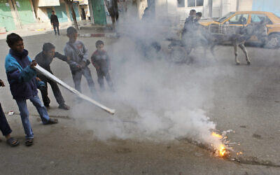 Children play with a flaming lump, allegedly containing white phosphorus, on a street in the town of Beit Lahiya, in the northern Gaza strip, January 19, 2009. (AP Photo/Ben Curtis, File)