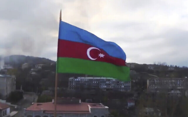 This photo taken from a video released by Azerbaijan's Defense Ministry on Monday, Nov. 9, 2020, shows Azerbaijan's national flag with the city of Shushi in the background, in the separatist region of Nagorno-Karabakh. President Ilham Aliyev said Sunday that Azerbaijani forces had taken control of the strategically important city in Nagorno-Karabakh, where fighting with Armenia has raged for over a month. (Azerbaijan's Defense Ministry via AP)