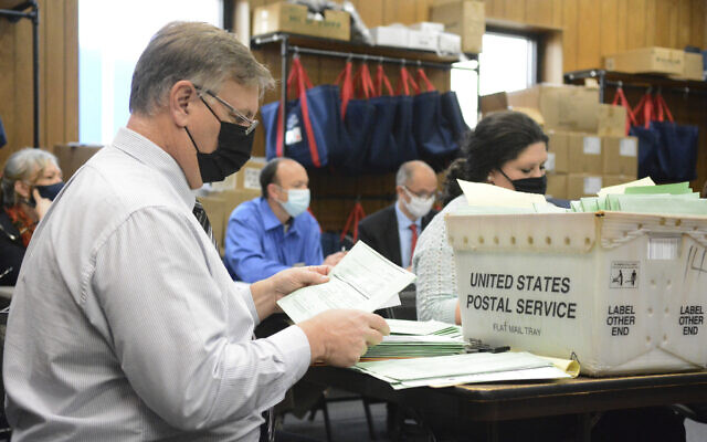 Election Bureau Director Albert L. Gricoski, left, opens provisional ballots alongside election bureau staff Christine Marmas, right, while poll watchers observe from behind at the Schuylkill County Election Bureau in Pottsville, Pa. on Tuesday, Nov. 10, 2020. (Lindsey Shuey/The Republican-Herald via AP)