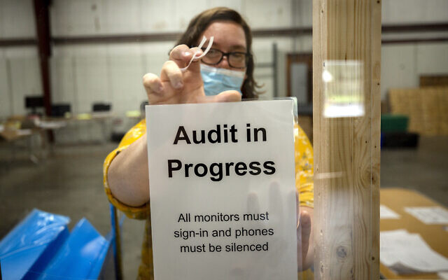 A Chatham County election official posts a sign in the public viewing area before the start of a ballot audit on November 13, 2020, in Savannah, Georgia. (AP/Stephen B. Morton)