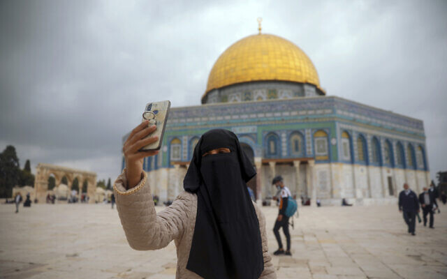 A Muslim woman takes a photo next to the Dome of the Rock Mosque in the Al Aqsa Mosque compound in Jerusalem's old city, November 6, 2020. (AP Photo/Mahmoud Illean)
