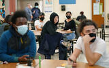 Students at West Brooklyn Community High School listen to questions posed by their principal during a current events-trivia quiz and pizza party in the school's cafeteria in New York, October 29, 2020. (AP Photo/Kathy Willen, File)