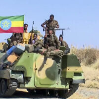 Screen capture from undated video released by the state-owned Ethiopian News Agency on November 16, 2020 shows Ethiopian military personnel sitting on an armored personnel carrier next to a national flag, on a road in an area near the border of the Tigray and Amhara regions of Ethiopia. (Ethiopian News Agency via AP)