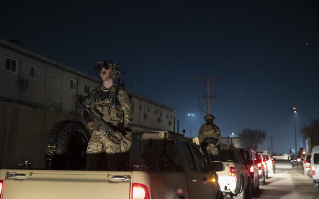 Armed US soldiers stand guard in the motorcade for President Donald Trump as he makes a surprise Thanksgiving Day visit to the troops at Bagram Air Field, Afghanistan. (AP Photo/Alex Brandon, File)