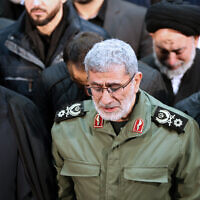 In this photo released by the official website of the Office of the Iranian Supreme Leader, Gen. Esmail Ghaani, newly appointed commander of Iran's Revolutionary Guards Quds Force, weeps while praying over the coffin of the force's previous head Gen. Qassem Soleimani at the Tehran University Campus in Tehran, Iran on January 6, 2020.  (Office of the Iranian Supreme Leader via AP)