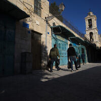 Palestinians walk past closed stores near the Church of the Nativity in the West Bank City of Bethlehem, Monday, November 23, 2020. (AP Photo/Majdi Mohammed)