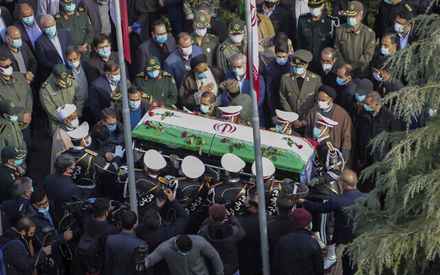 In this photo released by the official website of the Iranian Defense Ministry, military personnel carry the flag draped coffin of Mohsen Fakhrizadeh, a scientist who was killed on Friday, in a funeral ceremony in Tehran, Iran, Nov. 30, 2020 (Iranian Defense Ministry via AP)