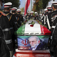 Military personnel stand near the flag-draped coffin of Mohsen Fakhrizadeh, during a funeral ceremony in Tehran, Iran, November 30, 2020. (Iranian Defense Ministry via AP)