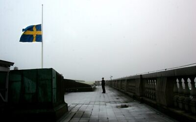 A security guard stands at attention after lowering the Swedish flag to half-staff on the roof of the Swedish parliament the Riksdag, in Stockholm, Sweden, January 1 2005. (AP Photo/Pressens Bild, Jack Mikrut)