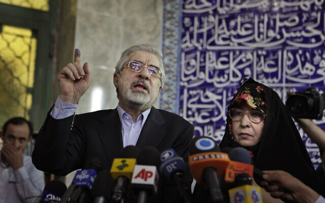 Leading challenger and reformist candidate Mir Hossein Mousavi speaks to the media after casting his vote with his wife Zahra Rahnavard, right, in the Iranian presidential elections at the Ershad mosque, on the outskirts of Tehran, Iran, June 12, 2009. (AP Photo/Ben Curtis)