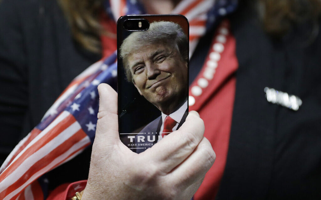 A woman holds up her cell phone before a rally with then presidential candidate Donald Trump in Bedford, New Hampshire, September 29, 2016. (AP Photo/John Locher, File)