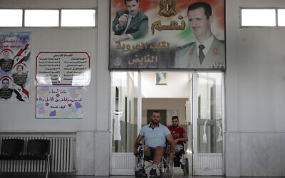 In this Sunday, Oct. 7, 2018 photo, Syrian soldiers who lost their legs while fighting in Syria's war, wheel past a poster showing Syrian President Bashar Assad, after a physical therapy session at the Ahmad Hamish Martyr hospital, in Damascus, Syria. (AP/Hassan Ammar)