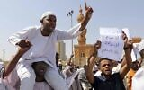 A man holds a poster with Arabic that reads, 'We will not give up, we will not sell out, we will not agree on normalization,' as others chant slogans to protest Sudanese President of the Sovereignty Council Abdel Fattah Abdelrahman Burhan's contentious decision to meet Prime Minister Benjamin Netanyahu in a move toward normalizing relations, in Khartoum, Sudan, Feb. 7, 2020. (AP Photo/Marwan Ali)