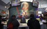 ILLUSTRATIVE -- An image of 'Crypto,' the main character in the video game 'Destroy All Humans!,' appears above people playing video games at the THQ Nordic exhibit, Feb. 27, 2020, at the Pax East conference in Boston. (AP Photo/Steven Senne)