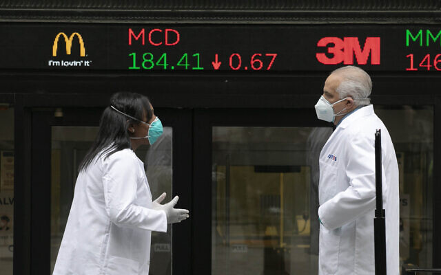 Healthcare screeners talk outside the New York Stock Exchange, as the trading floor partially reopens on May 26, 2020, in New York (Mark Lennihan/AP Images for THE NEW YORK STOCK EXCHANGE )
