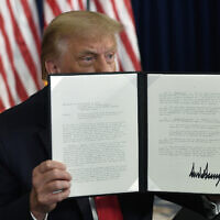 US President Donald Trump signs an executive order during a news conference at the Trump National Golf Club in Bedminster, N.J., Saturday, Aug. 8, 2020. (AP/Susan Walsh)