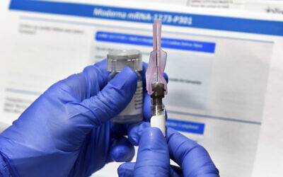 In this July 27, 2020, photo, a nurse prepares a shot as a study of a possible COVID-19 vaccine, developed by the National Institutes of Health and Moderna Inc., gets underway in Binghamton, New York. (AP Photo/Hans Pennink)