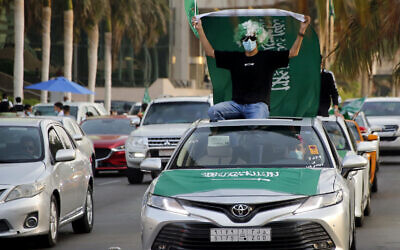 A Saudi waves a national flag during celebrations marking National Day to commemorate the unification of the country as the Kingdom of Saudi Arabia, in Jiddah, Saudi Arabia, Sept. 23, 2020. (AP/Amr Nabil)