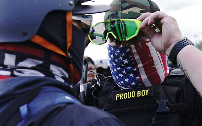 A member of the Proud Boys, right, stands in front of a counter protester as members of the Proud Boys and other right-wing demonstrators rally on September 26, 2020, in Portland. (AP Photo/John Locher)