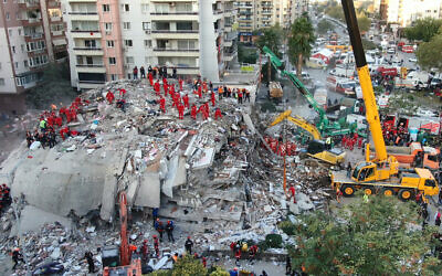 In this photo taken with a drone members of rescue services search for survivors in the debris of collapsed buildings in Izmir, Turkey, Oct. 31, 2020 (Ali Aksoyer/DHA via AP)