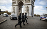 Police officers patrol by the Arc de Triomphe near the Champs Elysees avenue in Paris, Oct. 31, 2020 (AP Photo/Lewis Joly)